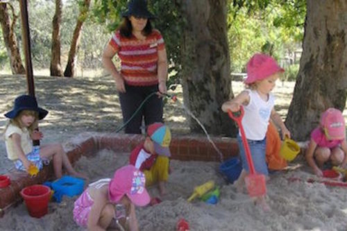 preschool teacher filling a bucket of water with a hose while kids play in the sand
