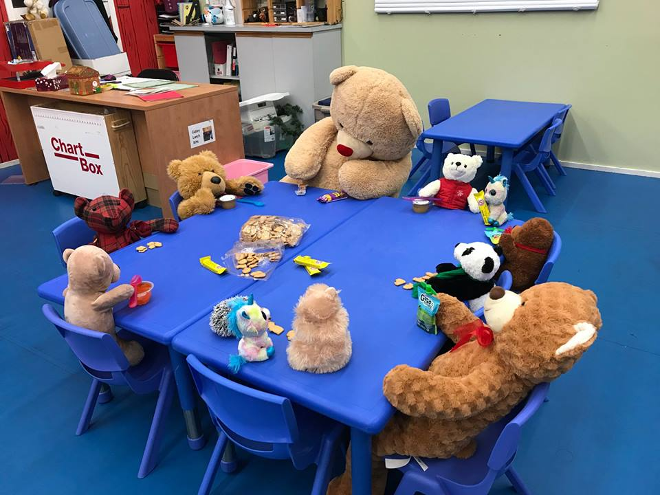 stuffed animals sitting around a table